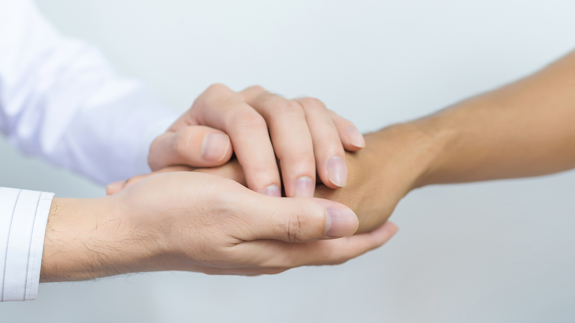 Two People Holding Hands For Comfort. Doctor Consoling Relatives_1528464043606
