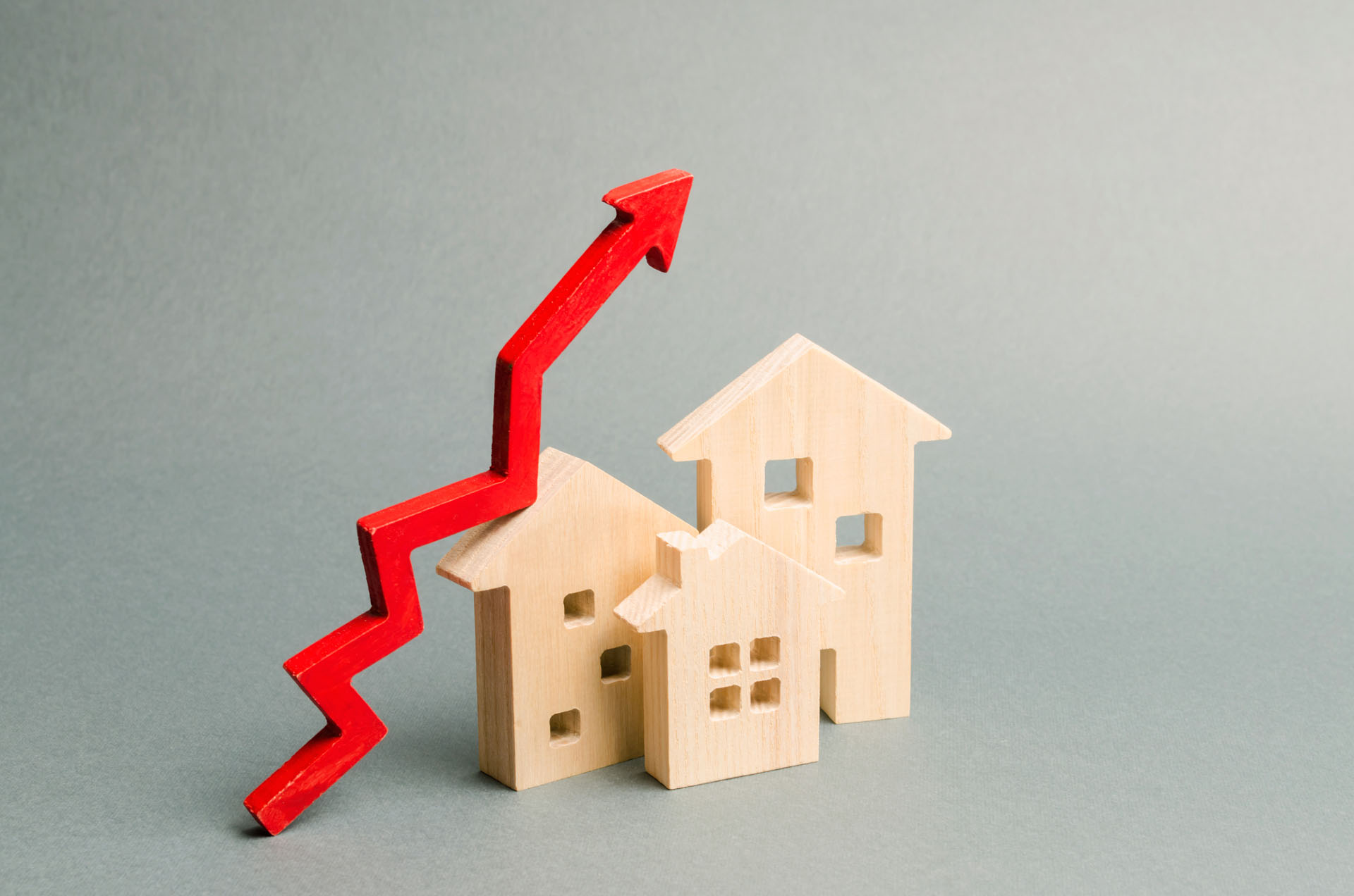 Miniature Wooden Houses And Red Arrow Up Population